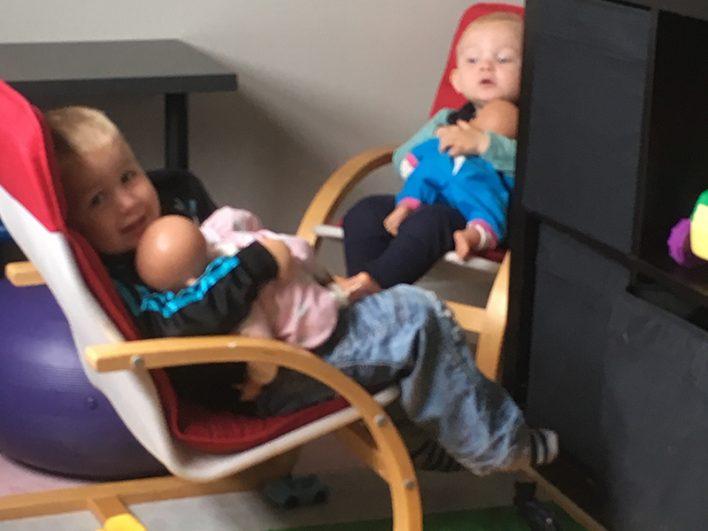 Børn der leger med dukker